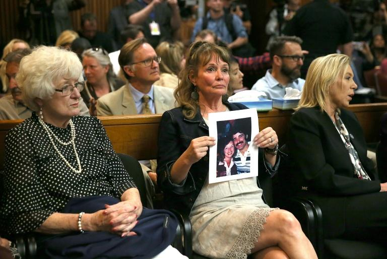 """An attendee holds a photo of Cheri Domingo and her boyfriend Gregory Sanchez, killed in 1981, during the arraignment of Joseph James DeAngelo, the suspected """"Golden State Killer"""" on April 27, 2018 in Sacramento (AFP Photo/JUSTIN SULLIVAN)"""