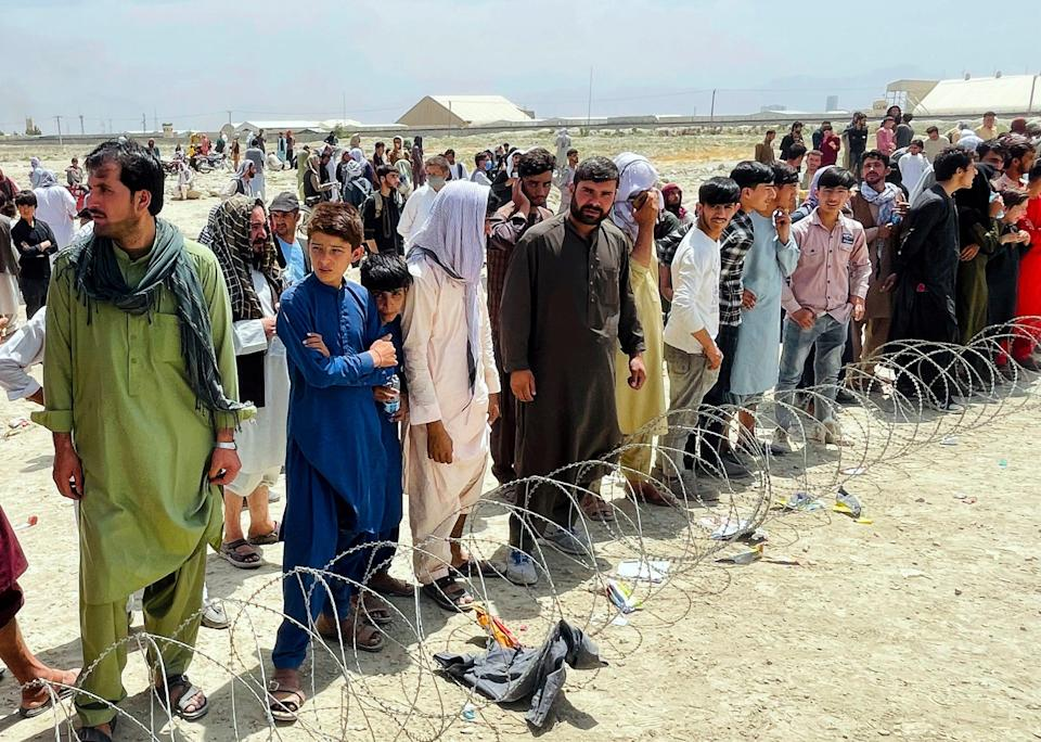 """Hundreds of people gather outside the international airport in Kabul, Afghanistan, on Aug. 17, 2021. The Taliban declared an """"amnesty"""" across Afghanistan and urged women to join their government Tuesday, seeking to convince a wary population that they have changed a day after deadly chaos gripped the main airport as desperate crowds tried to flee the country."""