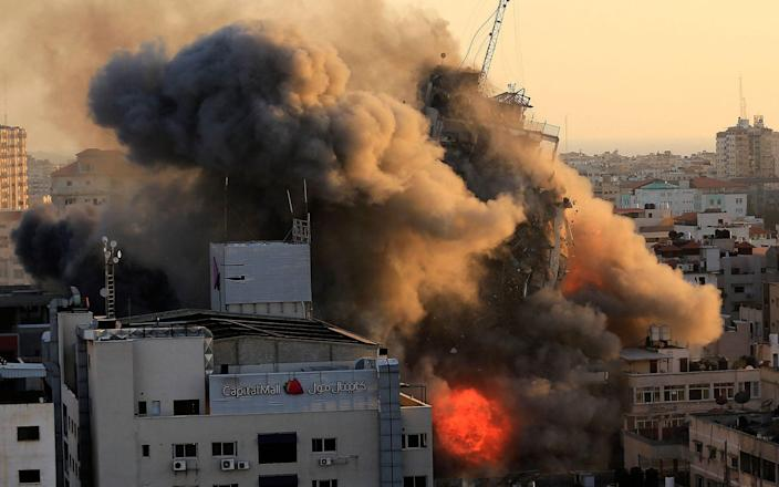Smoke billows from a tower block after an Israeli air strike - AFP