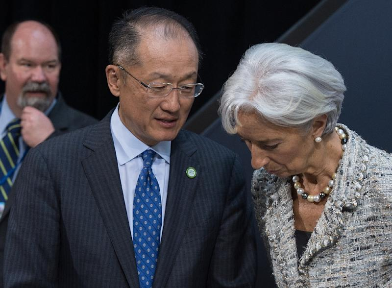 World Bank President Jim Yong Kim speaks with International Monetary Fund (IMF) Director General Christine Lagarde, at the IMF/WB Spring Meetings in Washington, DC, on April 17, 2015 (AFP Photo/Nicholas Kamm)