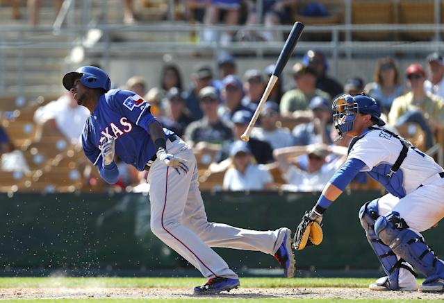 Texas Rangers Jurickson Profar throws his bat as Los Angeles Dodgers catcher Tim Federowicz watches during an exhibition baseball game in Glendale, Ariz., Friday, March 7, 2014. Profar grounded out on the at-bat. (AP Photo/Paul Sancya)