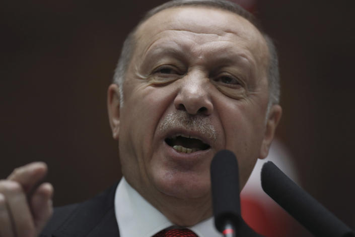 Turkish President Recep Tayyip Erdogan addresses his ruling party members at the parliament, in Ankara, Turkey, Wednesday, Feb. 12, 2020. Erdogan said Wednesday that Turkey will attack government forces anywhere in Syria if another Turkish soldier is injured. (AP Photo/Burhan Ozbilici)
