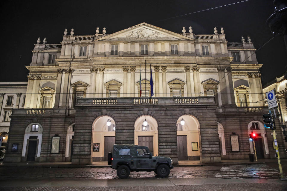A military vehicle drives past La Scala opera theater in Milan, northern Italy, early Sunday, Oct. 25, 2020. Since the 11 p.m.-5 a.m. curfew took effect last Thursday, people can only move around during those hours for reasons of work, health or necessity. (AP Photo/Luca Bruno)