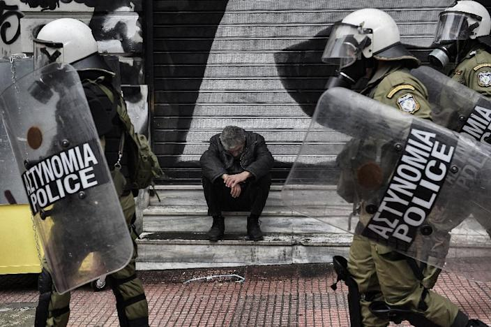 A man sits outside a closed store as demonstrators clash with riot police in Athens, on February 4, 2016 (AFP Photo/Aris Messinis)