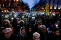 FILE - In this Thursday, March 15, 2018 file photo, people taking part in a march against Prime Minister Viktor Orban flash the lights of their mobile phones in Budapest, Hungary. When Hungary and Poland joined the European Union in 2004, after decades of Communist domination, they thirsted for Western democratic standards and prosperity yet, 17 years later, as the EU ramps up efforts to rein in democratic backsliding in both countries, some of the governing right-wing populists in Hungary and Poland are comparing the bloc to their former Soviet oppressors — and flirting with the prospect of exiting the bloc. (AP Photo/Darko Vojinovic, File)
