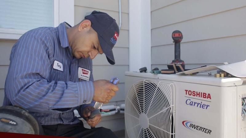 A technician from Kahn Air works to install a Carrier ductless heat pump at the Los Angeles home of Tamara as part of the donation Carrier made of more than 500 home comfort systems to Habitat for Humanity.