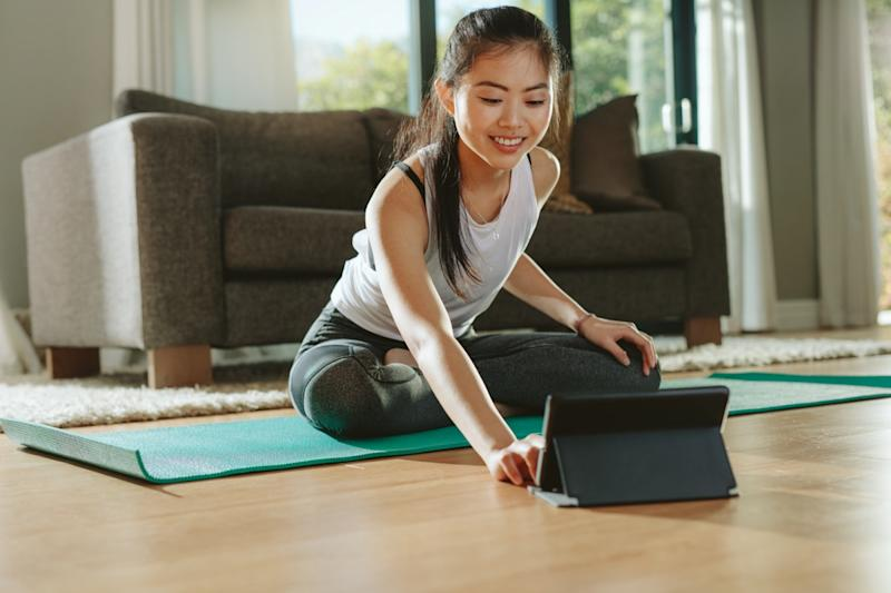 Smiling woman sitting exercise mat and watching training videos on digital tablet
