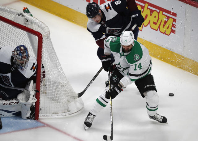 Dallas Stars left wing Jamie Benn, front right, loses control of the puck as Colorado Avalanche defenseman Cale Makar, back right, and goaltender Philipp Grubauer cover in the first period of an NHL hockey game Tuesday, Jan. 14, 2020, in Denver. (AP Photo/David Zalubowski)