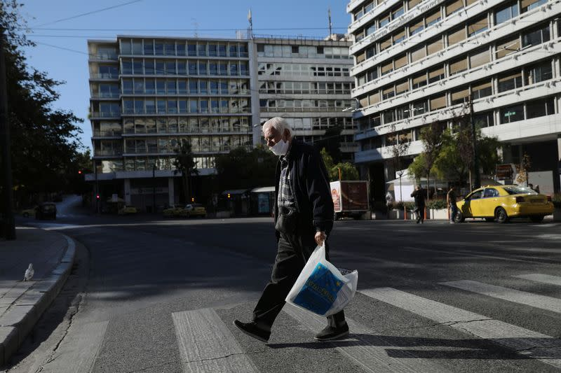 A pedestrian wearing a protective face mask walks on a zebra crossing, amid the spread of the coronavirus disease (COVID-19), in Athens