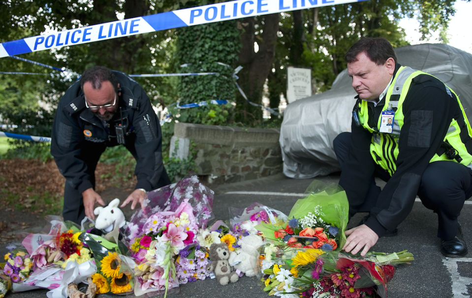 Police officers lay flowers at the scene of the killings in St Helier, Jersey, in 2011 (Picture: Rex)