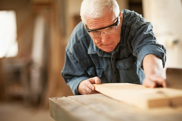 A senior man cutting a piece of lumber in a wood shop.