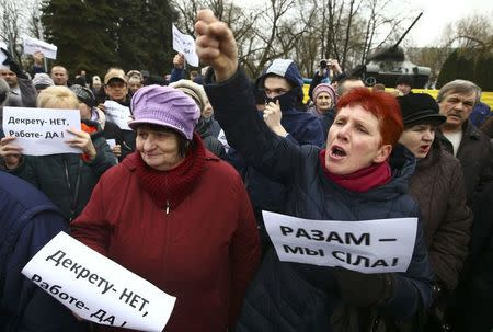 "People shout slogans during a protest against increased tariffs for communal services and new taxes, including the tax for those who are not in full-time employment, in the town of Bobruisk, Belarus March 12, 2017. The placards read, ""No to decree, yes to work!"" (L), ""Together we are a force!"" REUTERS/Vasily Fedosenko"