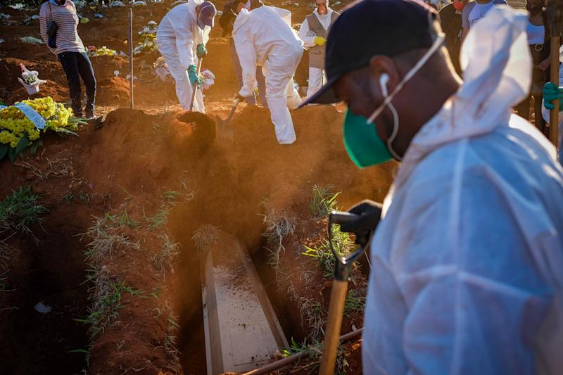 14 October 2020, Brazil, Sao Paulo: Cemetery workers in protective suits shovel soil onto a coffin during a funeral at the Vila Formosa cemetery in the middle of the Corona pandemic. The Ministry of Health has confirmed 955 377 Covid-19 infected and 46 510 coronavirus deaths. More than a quarter of the newly registered deaths occurred in the state of São Paulo. Photo: Lincon Zarbietti/dpa (Photo by Lincon Zarbietti/picture alliance via Getty Images)