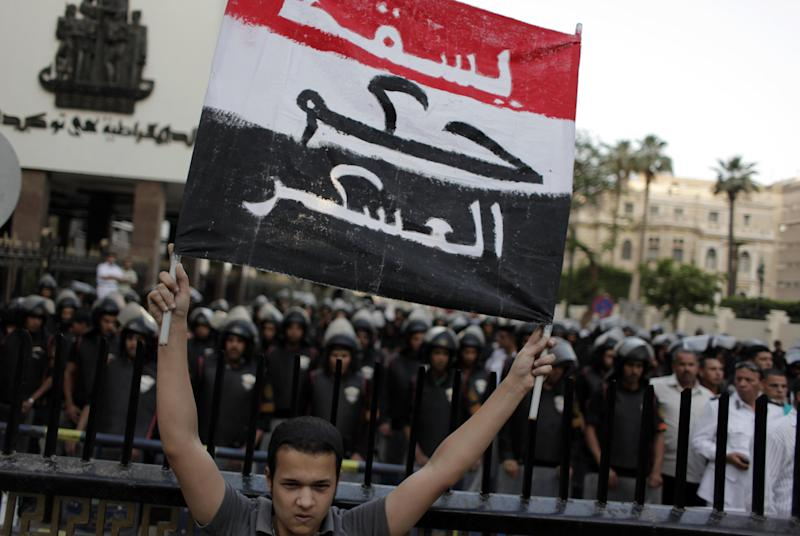 "A protester holds a placard in the colors of the Egyptian flag and Arabic that reads, ""down with the military rule,"" in front of riot police during a rally demanding the release of fellow activists, detained during the army operation that dispersed a protest in front of the Ministry of Defense, in Cairo, Egypt, Sunday, May 6, 2012. (AP Photo/Nasser Nasser)"