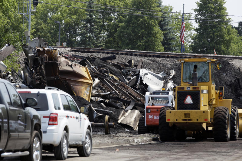 Emergency vehicles are shown at the scene in Northbrook, Ill., Friday, July 6, 2012, where a train derailment Wednesday caused the collapse of a bridge, killing two people in a car traveling under the bridge. Burton and Zorine Lindner, of Glenview, were driving under the railroad bridge when the train derailed. Twenty-eight rail cars hauling coal piled up on the bridge, causing it to collapse over a road between the suburbs of Glenview and Northbrook. A huge mound of twisted train cars and coal filled the gap where the bridge had been. (AP Photo/Nam Y. Huh)