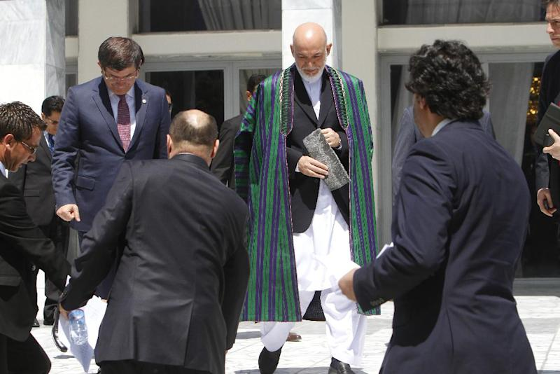 Afghan President Hamid Karzai, center, arrives for a group photo with the foreign attendees of the Asia Ministerial Conference at the foreign ministry in Kabul, Afghanistan, Thursday, June 14, 2012. Afghanistan's neighbors and regional heavyweights met in Kabul on Thursday to do something they rarely do _ try to tackle common threats and problems together.(AP Photo/Musadeq Sadeq)