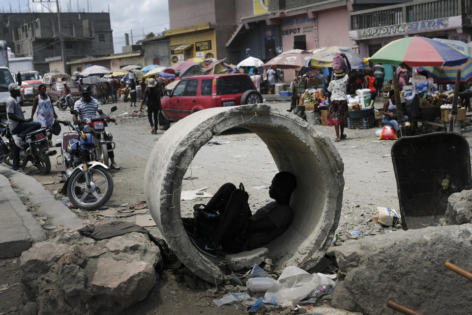 A man uses his cellphone inside a concrete pipe at a market in Cap-Haitien, Haiti, Thursday, July 22, 2021. The city of Cap-Haitien is holding events to honor slain President Jovenel Moïse on Thursday ahead of Friday's funeral. (AP Photo/Matias Delacroix)
