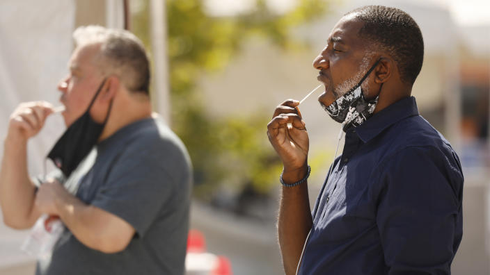 Charles Davis, 49, right, self administers the oral swab test during Coronavirus Covid-19 testing in LA County at the Charles R. Drew University of Medicine and Science in South Los Angeles on July 8, 2020. (Al Seib / Los Angeles Times via Getty Images)