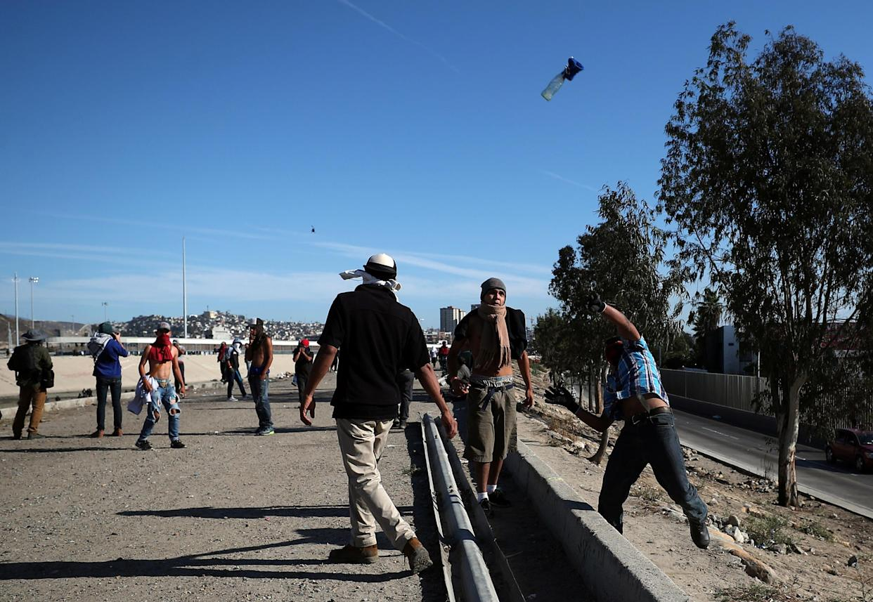 A migrant throws a glass bottle at U.S border patrol over the border fence between Mexico and the U.S. in Tijuana, Mexico, on Sunday. (Photo: Hannah McKay/Reuters)