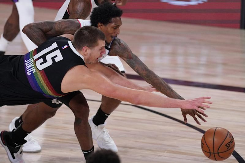 Denver Nuggets' Nikola Jokic reaches for the ball with Clippers' Lou Williams.