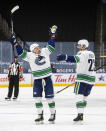 Vancouver Canucks' Jayce Hawryluk (13) and Alexander Edler (23) celebrate a goal against the Edmonton Oilers during the first period of an NHL hockey game Thursday, May, 6, 2021, in Edmonton, Alberta. (Jason Franson/The Canadian Press via AP)