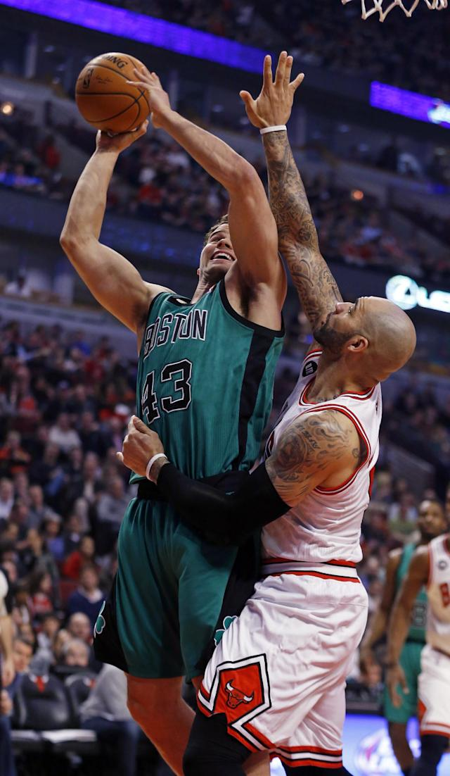 Boston Celtics center Kris Humphries, left, goes to the basket against Chicago Bulls forward Carlos Boozer, right, during the first half of an NBA basketball game in Chicago, Monday, March 31, 2014. (AP Photo/Kamil Krzaczynski)