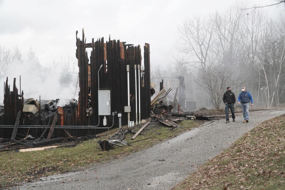 Two people walk past the remains of the Doris Duke Theatre at Jacob's Pillow in Becket, Mass., which burned in an early morning fire, Tuesday, Nov. 17, 2020. At the peak of the fire, about 30 firefighters worked to control the blaze. Departments from Hinsdale, Otis, Lee, Monterey and Chester assisted Becket. The Doris Duke Theatre is one of two indoor theaters on the grounds of Jacob's Pillow. (Ben Garver/The Berkshire Eagle via AP)