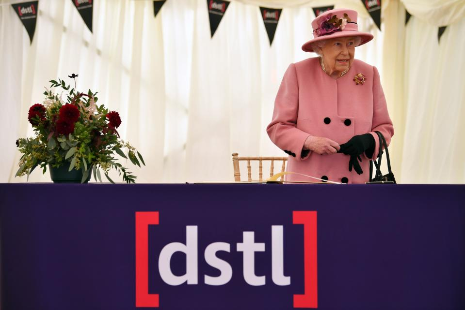 Britain's Queen Elizabeth II stands after signing a visitor's book during her visit to the Defence Science and Technology Laboratory (Dstl) at Porton Down science park near Salisbury, southern England, on October 15, 2020. - The Queen and the Duke of Cambridge visited the Defence Science and Technology Laboratory (Dstl) where they were to view displays of weaponry and tactics used in counter intelligence, a demonstration of a Forensic Explosives Investigation and meet staff who were involved in the Salisbury Novichok incident. Her Majesty and His Royal Highness also formally opened the new Energetics Analysis Centre. (Photo by Ben STANSALL / POOL / AFP) (Photo by BEN STANSALL/POOL/AFP via Getty Images)