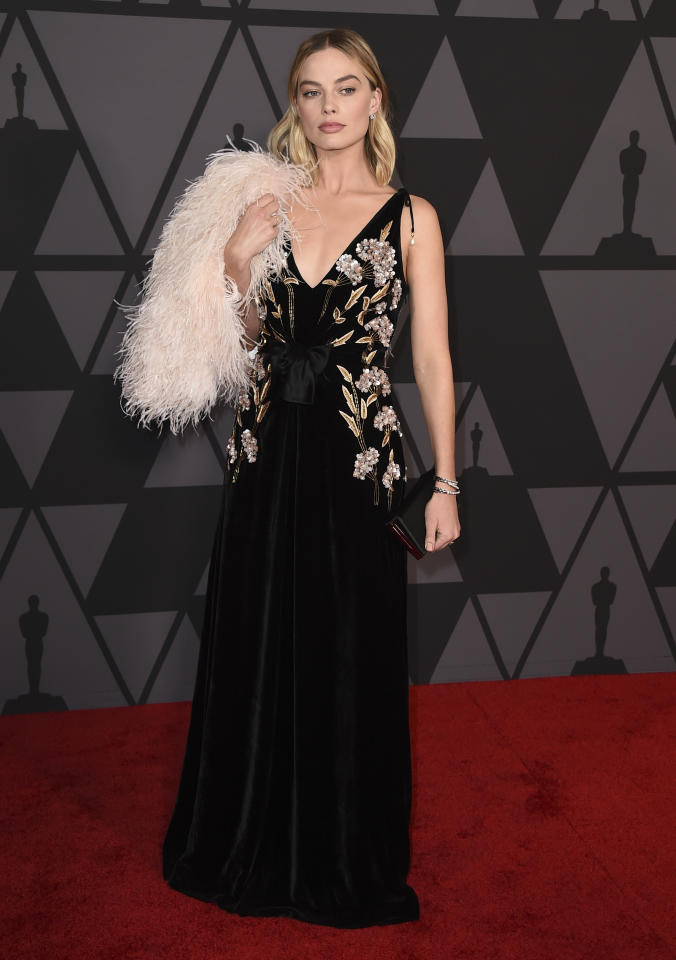 <p>Because Robbie didn't look chic enough already in a black gown with floral embroidery, she brought it to the next level with a fuzzy pink accessory. (Photo: Getty Images) </p>