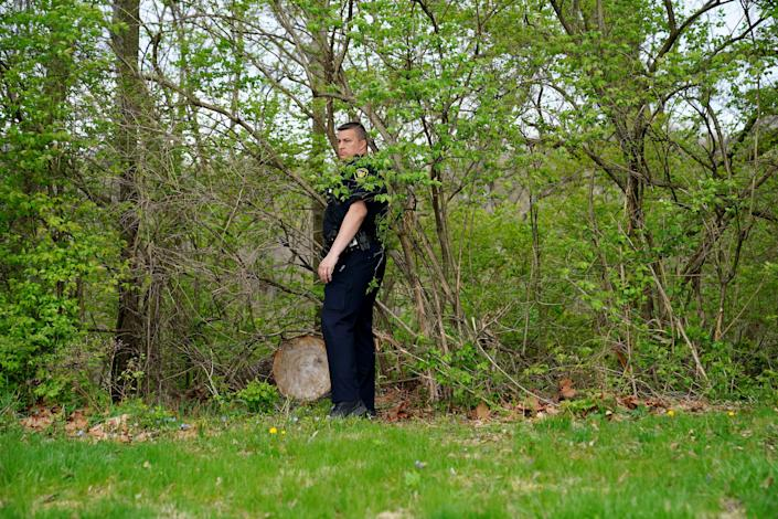 A Cincinnati Police officer searches a wooded area for monkeys reported to be on the loose, Thursday, April 8, 2021, at St. Joseph's Cemetery in the East Price Hill neighborhood of Cincinnati.