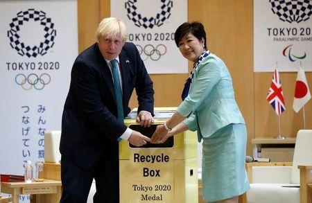Britain's Foreign Secretary Boris Johnson (L), flanked by Tokyo Governor Yuriko Koike, feeds a smartphone into a box collecting old mobile phones from Tokyo residents, which will be recycled into medals for the 2020 Tokyo Olympics and Paralympics, during their meeting at Tokyo Metropolitan Government buildingin Tokyo, Japan July 21, 2017. REUTERS/Issei Kato
