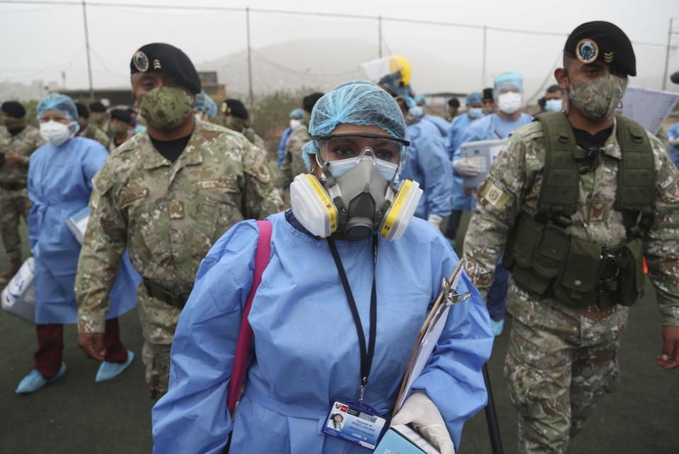 Health workers are escorted by soldiers during a house-to-house COVID-19 testing campaign in the Villa Maria del Triunfo shantytown of Lima, Peru, Tuesday, Jan. 12, 2021. As the number of infected continues to rise in Peru, soldiers are assisting with compliance and security during a massive testing effort across the capital. (AP Photo/Martin Mejia)