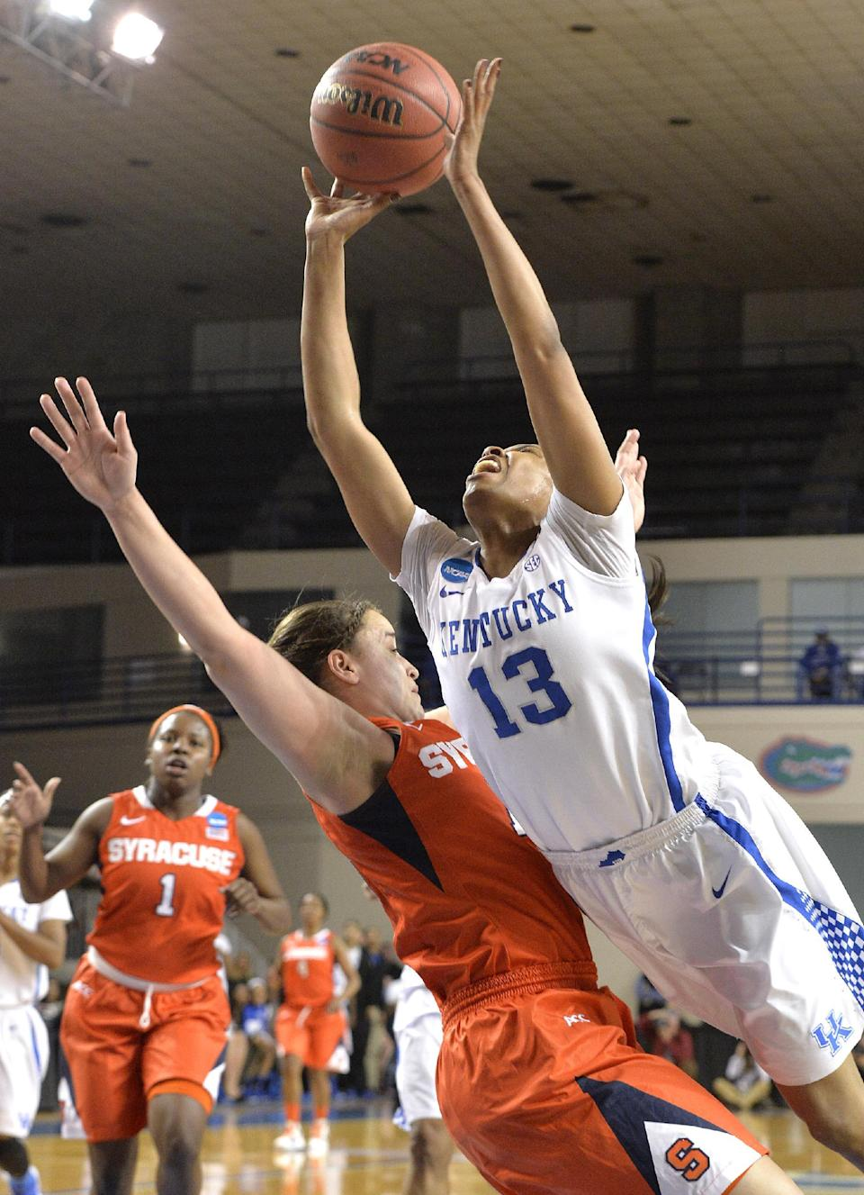 Kentucky's Bria Goss, right, puts up a shot while being blocked by Syracuse' Brianna Butler during the first half of a second-round game in the NCAA college basketball tournament in Lexington, Ky., Monday, March 24, 2014. Kentucky defeated Syracuse 64-59. (AP Photo/Timothy D. Easley)