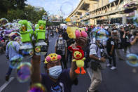 CORRECTS PHOTOGRAPHER'S NAME - A man holds up bubble blowers and merchandise designed as yellow ducks, which have become good-humored symbols of resistance during anti-government rallies, Friday, Nov. 27, 2020 in Bangkok, Thailand. Pro-democracy demonstrators are continuing their protests calling for the government to step down and reforms to the constitution and the monarchy, despite legal charges being filed against them and the possibility of violence from their opponents or a military crackdown. (AP Photo/Wason Wanichakorn)