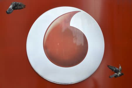 Pigeons fly past Vodafone branding outside a retail store in London