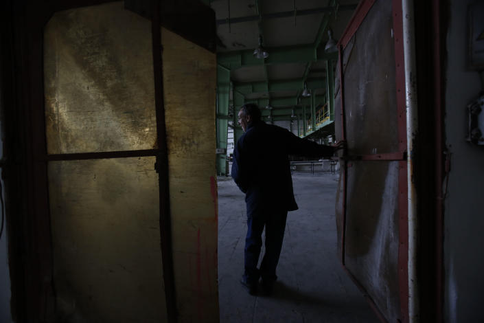 """An employee of the detergent factory """"Dita"""" opens a door inside the factory in the Bosnian town of Tuzla, 140 kms north of Sarajevo on Wednesday, Feb. 12, 2014. The violence engulfing Bosnia in recent days, with scenes of burning government buildings and protesters pelting police with stones, has many root causes. One of them is the failed privatizations of state-owned companies. (AP Photo/Amel Emric)"""