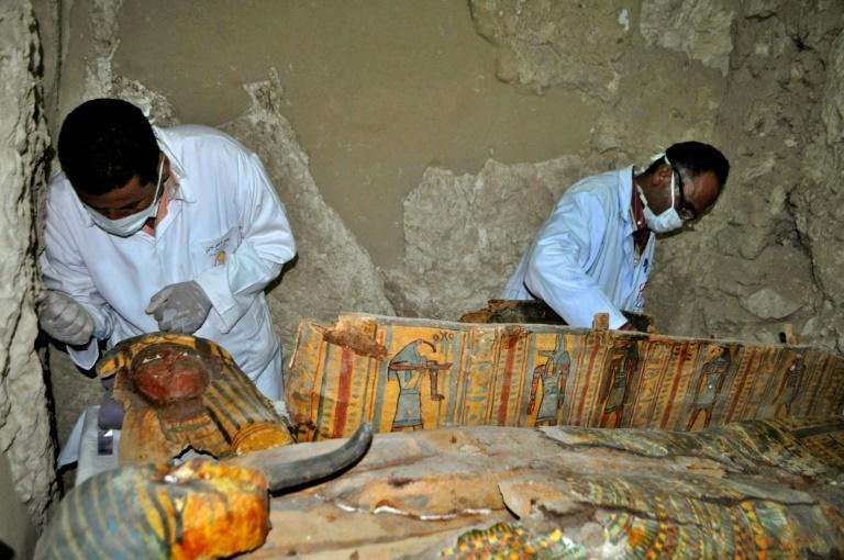 Members of an Egyptian archaeological team work on April 18, 2017 on a wooden coffin discovered in a 3,500-year-old tomb in the Draa Abul Nagaa necropolis, near the southern Egyptian city of Luxor