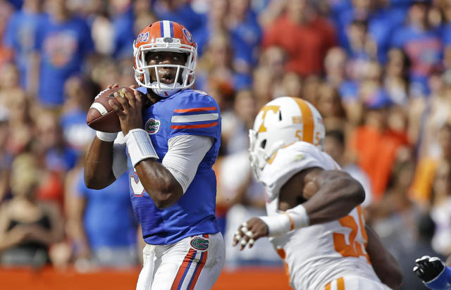 Florida quarterback Tyler Murphy, left, looks for a receiver as he is pressured by Tennessee defensive lineman Jacques Smith (55) during the first half of an NCAA college football game in Gainesville, Fla., Saturday, Sept. 21, 2013.(AP Photo/John Raoux)