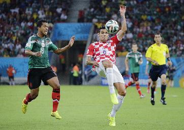 Mexico's Giovani dos Santos, left, challenges Croatia's Dejan Lovren during the group A World Cup soccer match between Croatia and Mexico at the Arena Pernambuco in Recife, Brazil, Monday, June 23, 2014. (AP Photo/Sergei Grits)