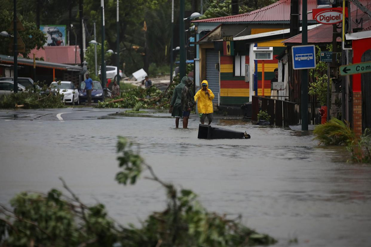People walk in a flooded street in Pointe-a-Pitre, Guadeloupe, on Sept. 19, 2017.
