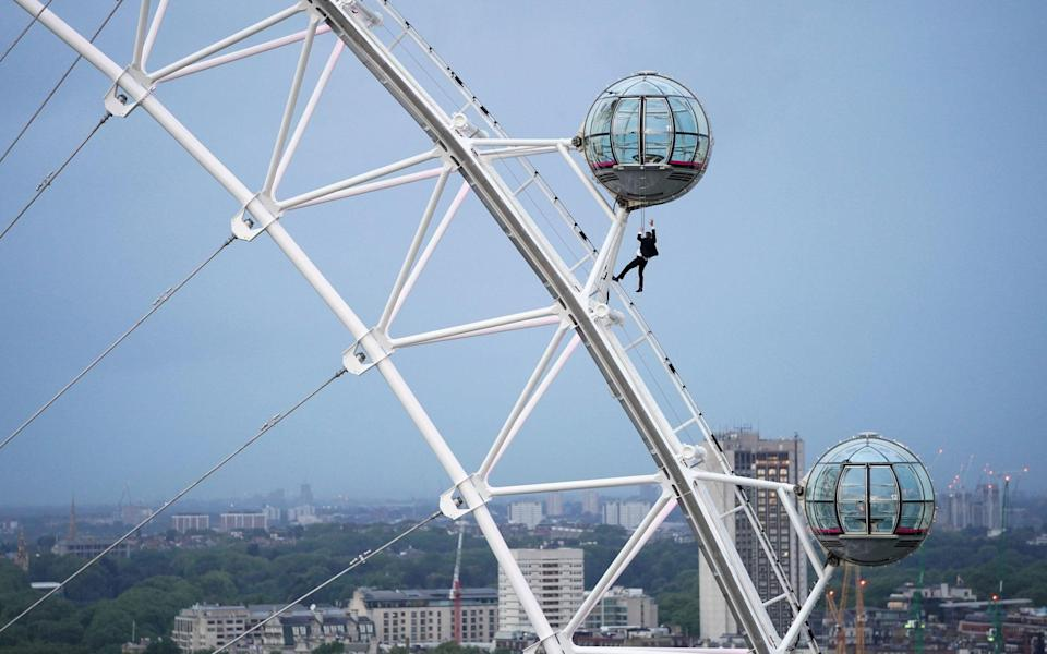 A man dressed as James Bond hangs from a pod on the London Eye ahead of the world premiere of No Time To Die