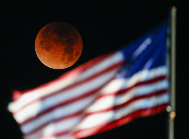 <p>A rare occurrence called a 'Super Blue Blood Moon' is seen behind the U.S. flag at Santa Monica Beach in Santa Monica, Calif., Wednesday, Jan. 31, 2018. (Photo: Ringo H.W. Chiu/AP) </p>