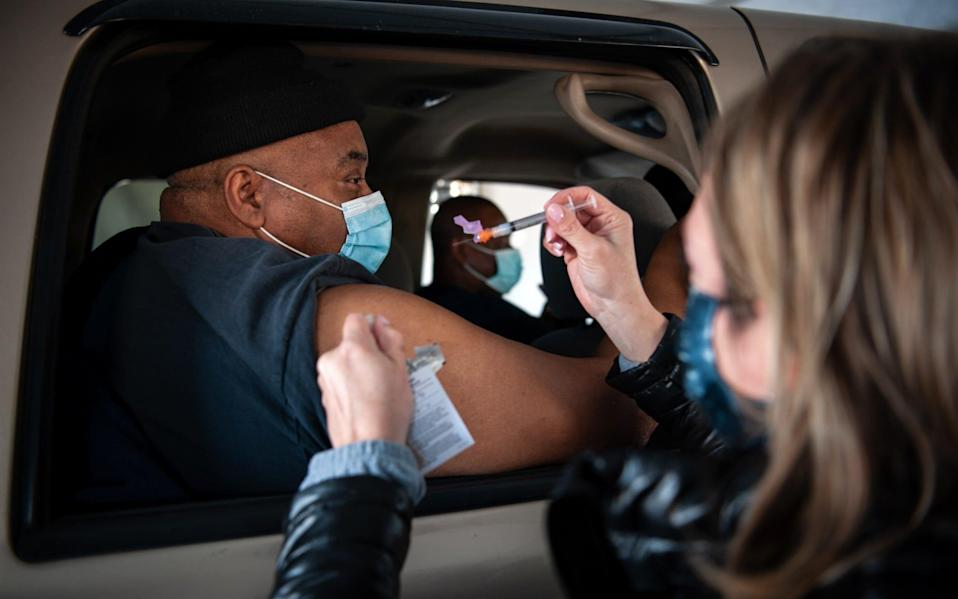 A healthcare worker administers a dose of the Moderna vaccine at a medical centre drive-thru site in Greenville, Mississippi - Bloomberg