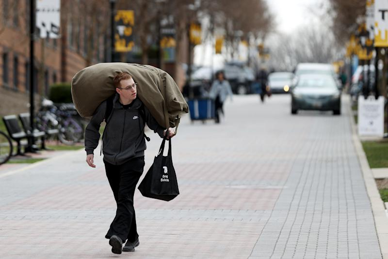 TOWSON, MARYLAND - MARCH 11: Towson University student Garrett Lang of Frederick, Maryland carries his belongings out of the dorms as the school shut down days before the start of the scheduled spring break on March 11, 2020 in Towson, Maryland. Universities across the nation have closed through spring break as the novel Coronavirus spreads. (Photo by Rob Carr/Getty Images)