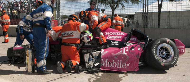 Safety team members work to remove Dario Franchitti, of Scotland, from his car after a crash during the second IndyCar Grand Prix of Houston auto race, Sunday, Oct. 6, 2013, in Houston. (AP Photo/Juan DeLeon)
