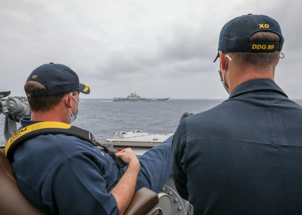 A US Navy commander and his colleague watch a Chinese aircraft carrier sail by.