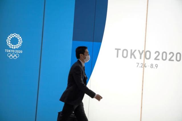 FILE PHOTO: A man wearing a protective face mask, following an outbreak of the coronavirus, walks past an advertising billboard of Tokyo Olympics 2020, near the Shinjuku station in Tokyo