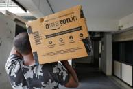 A delivery worker of Amazon carries a packet to deliver it to a customer at a residential apartment in Ahmedabad