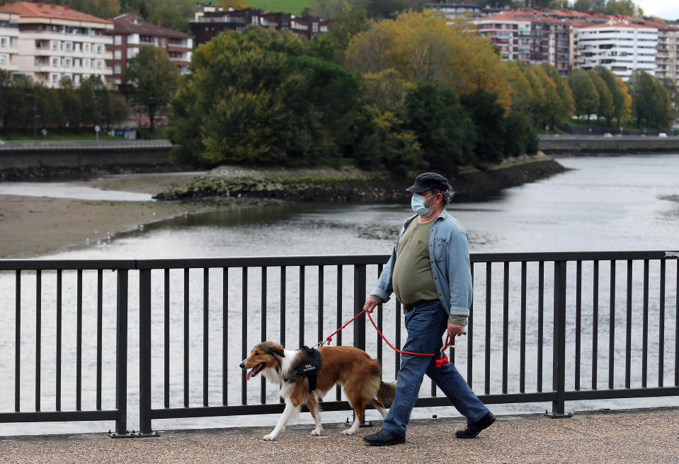 A man wearing a face mask crosses the Bidassoa river between France and Spain at Behobie, southwestern France, Thursday, Oct.22, 2020. France has seen over 34,000 confirmed deaths in the pandemic. (AP Photo/Bob Edme)