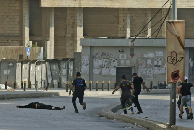 Fighters from the Shiite Hezbollah and Amal movements rush to the body of a fallen comrade during clashes in Beirut's Tayouneh area (AFP/JOSEPH EID)